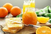 Jar of orange marmalade and bread on a wooden cutting board