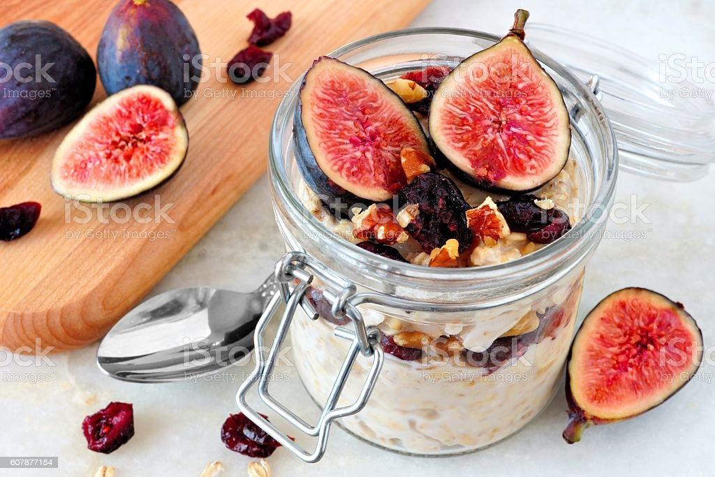 Jar of overnight autumn oats with figs, cranberries and walnuts stock photo