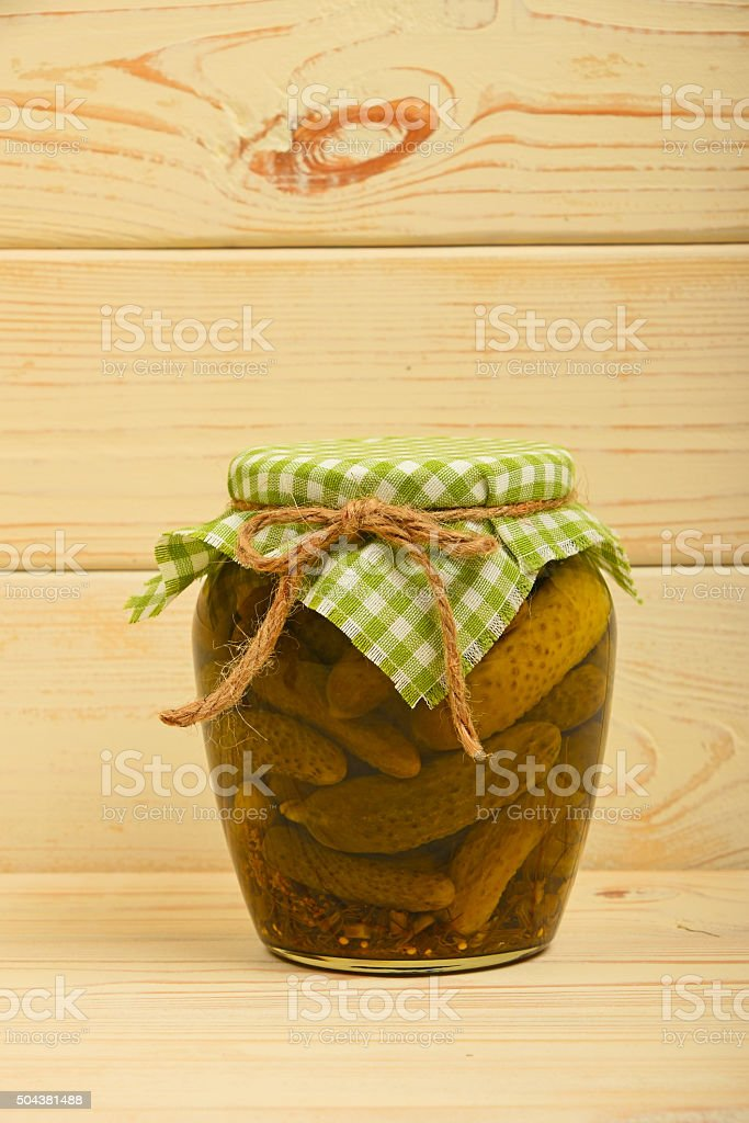 Jar of pickled cucumbers at vintage wood surface royalty-free stock photo