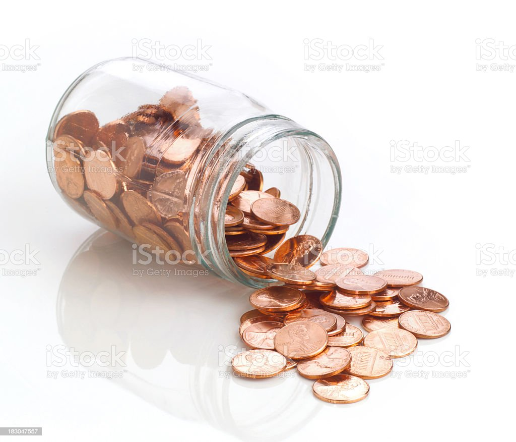 Jar of polished US pennies spilling out on white stock photo