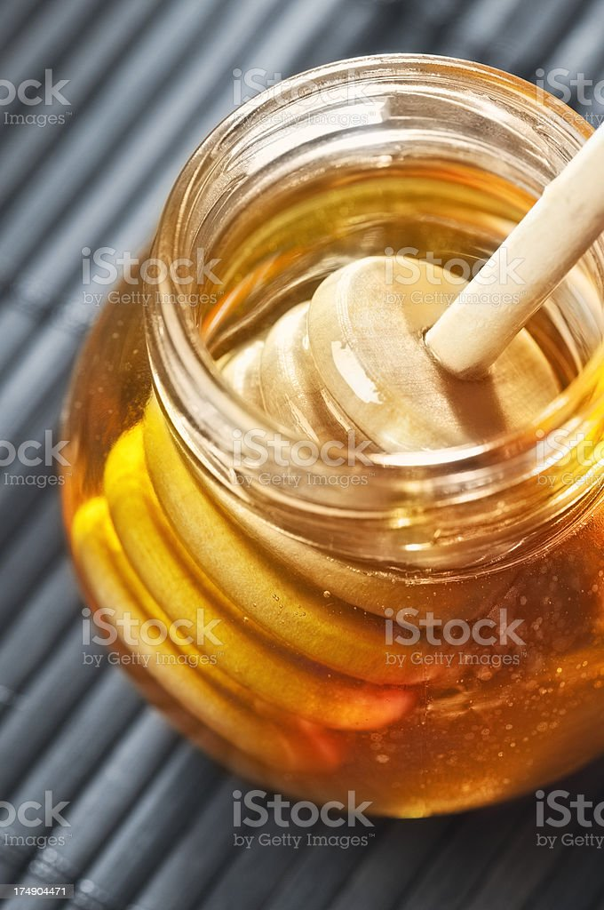 Jar of pure golden honey with a wooden honey drizzler royalty-free stock photo