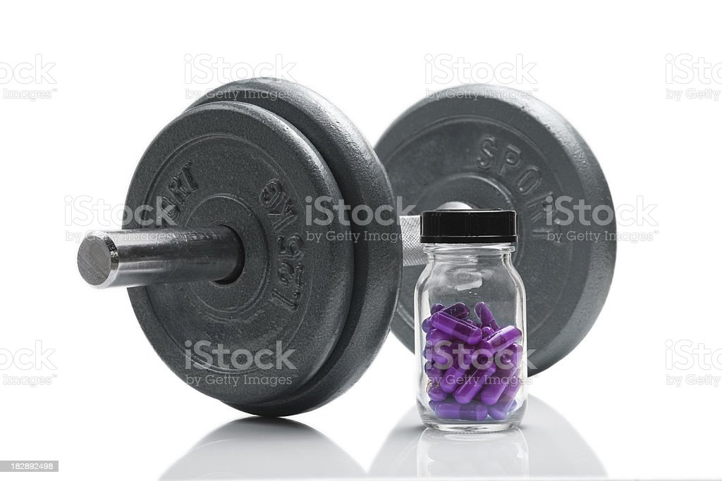 Jar of purple anabolic steroids next to a dumbbell royalty-free stock photo
