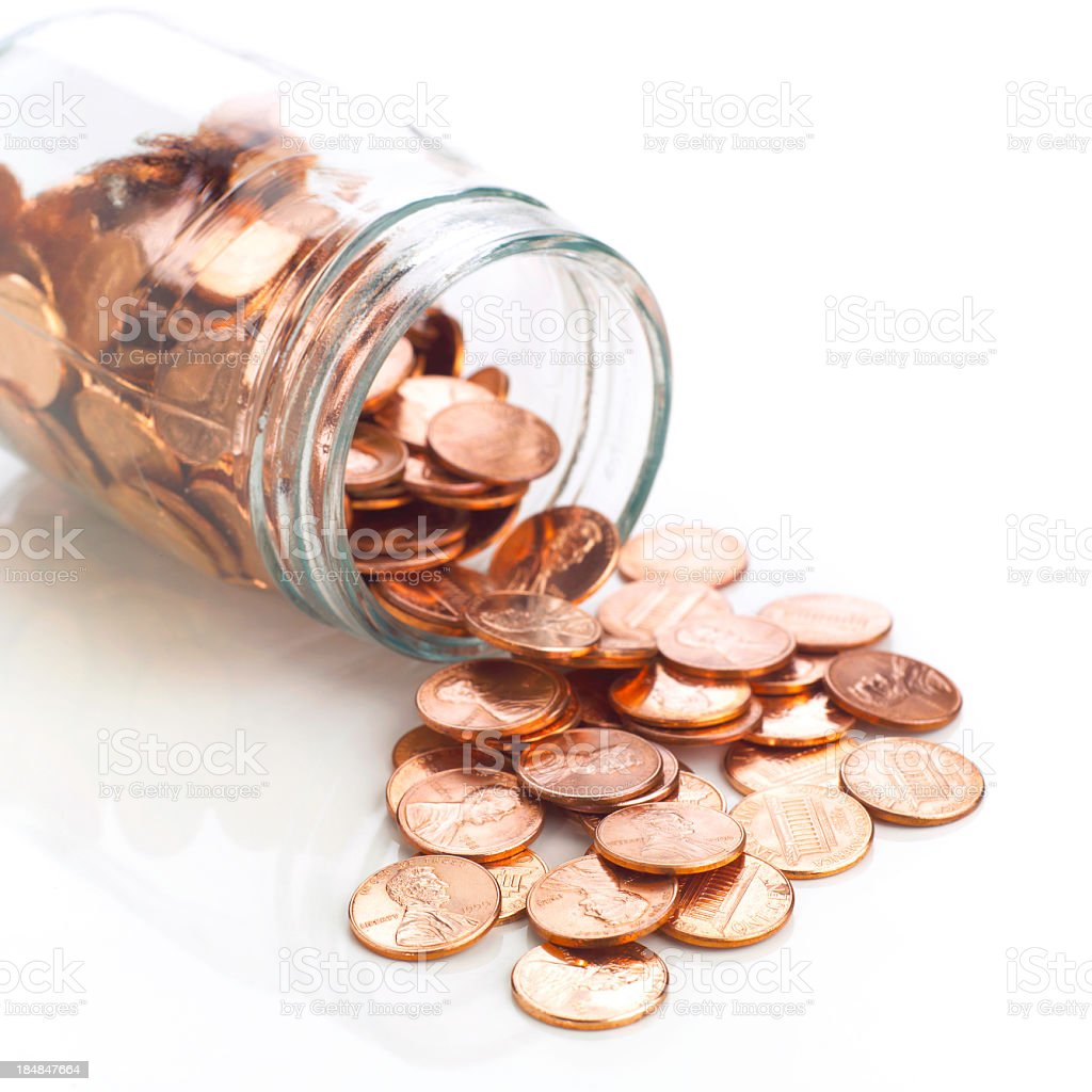 Jar of shiny US pennies spilling out on refective white stock photo