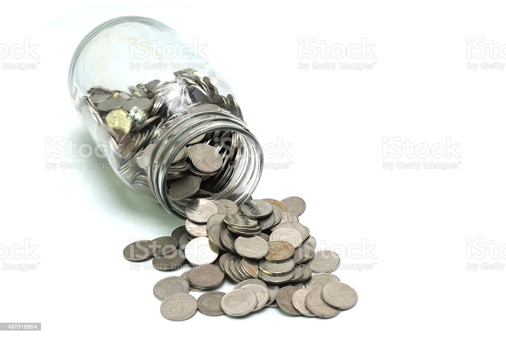 Jar of thai coins spilled on a white background stock photo