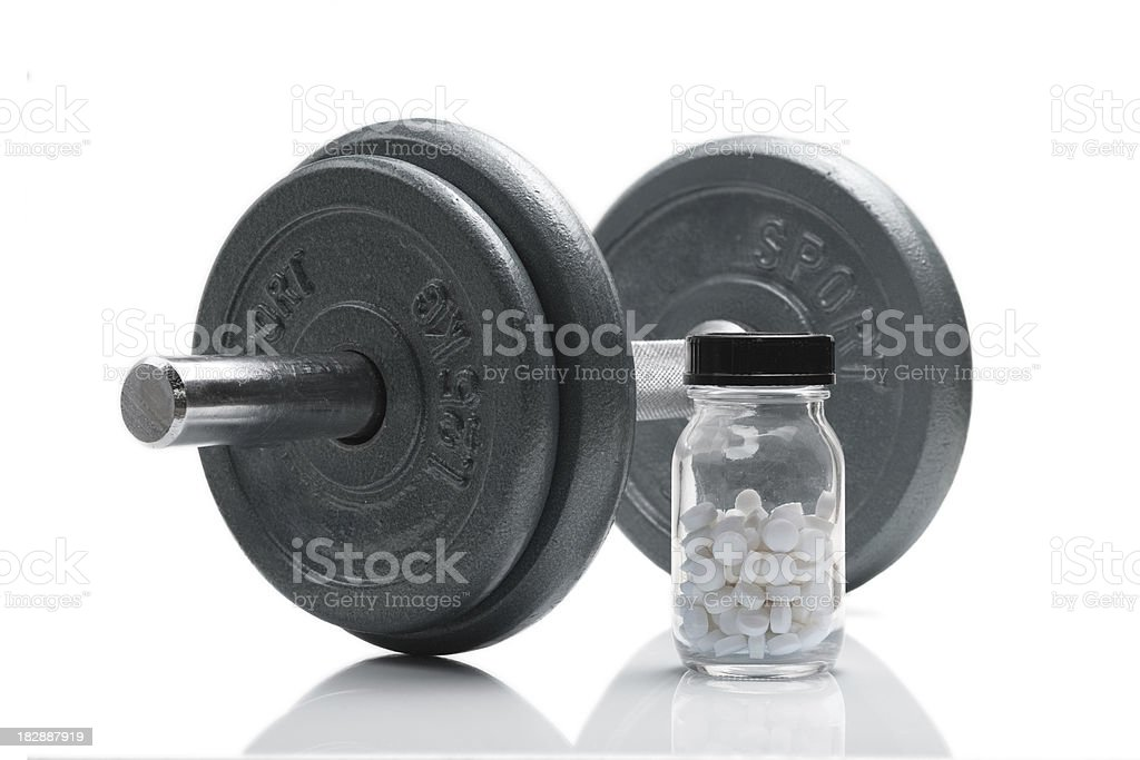 Jar of white anabolic steroids next to a dumbbell stock photo