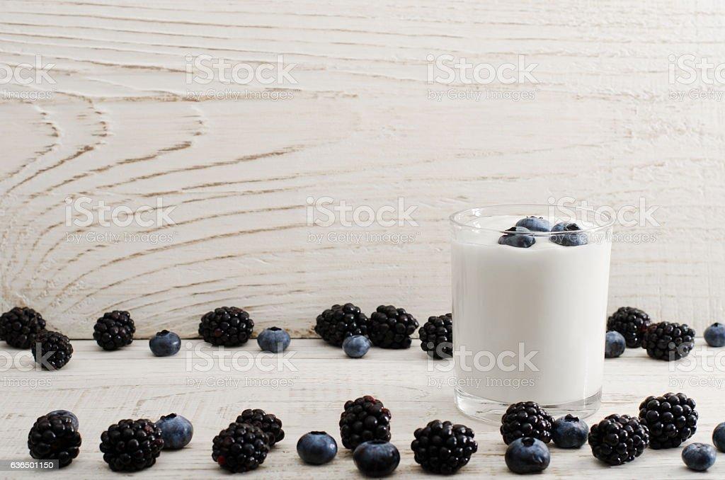 Jar of yogurt with blueberries and blackberries stock photo