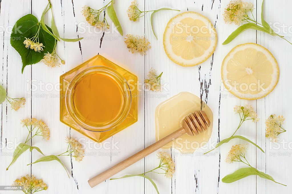Jar with honey and linden flowers on rustic wooden table stock photo