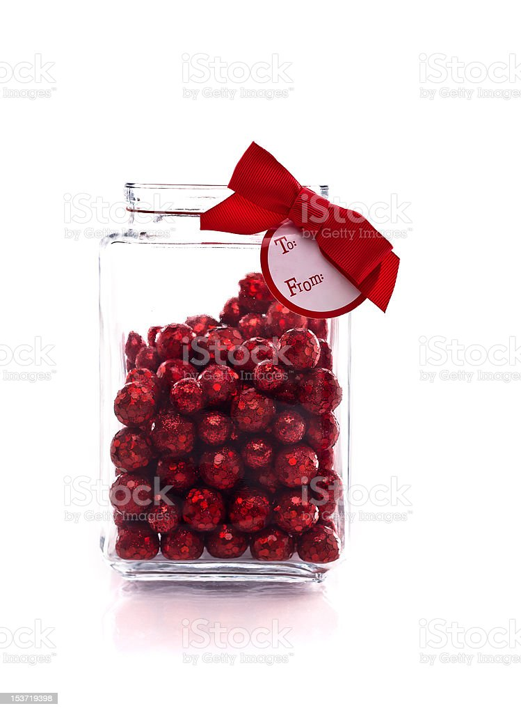 Jar with red glittery candy, and gift tag royalty-free stock photo
