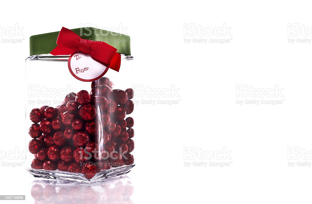 Jar with red glittery candy, green lid and gift tag royalty-free stock photo
