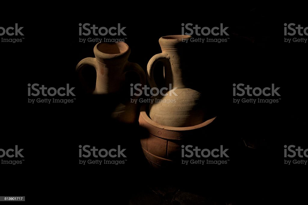 Jars / amphorae emerge from the shadows stock photo