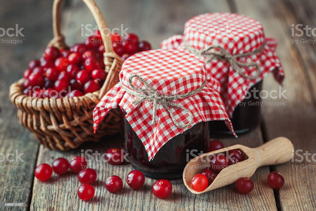 Jars of cranberries jam and basket with bog berry stock photo