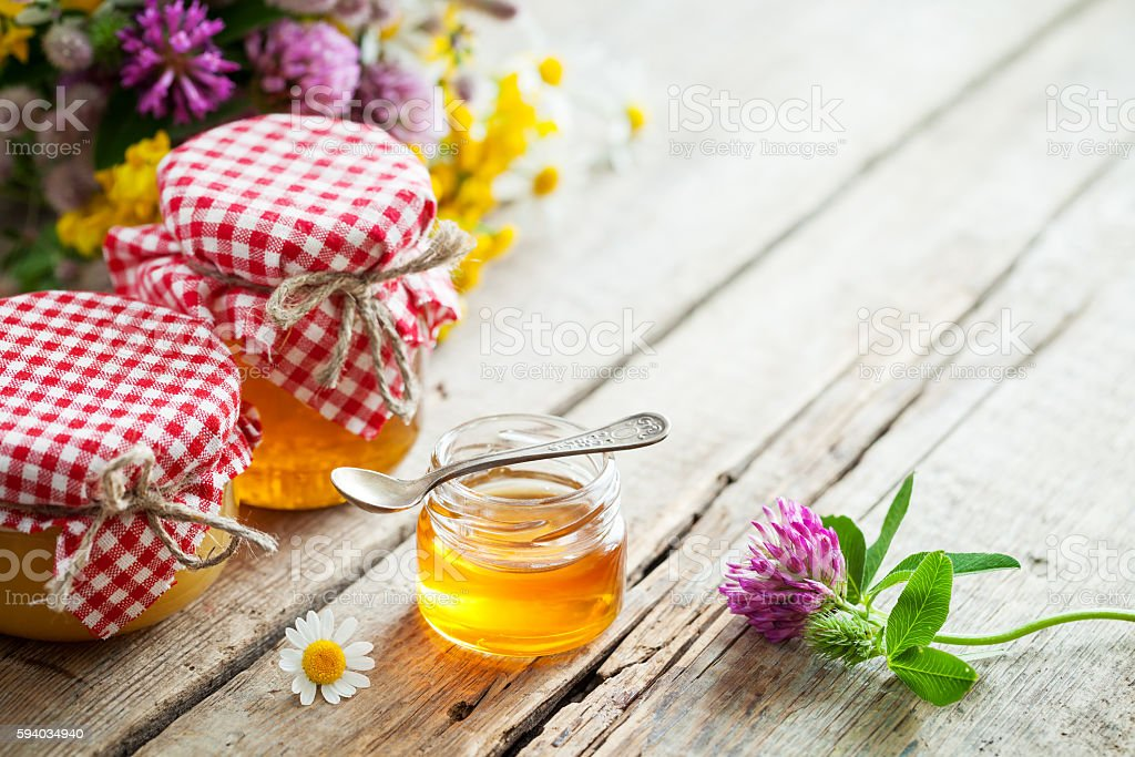 Jars of honey and healing herbs bunch on table. stock photo