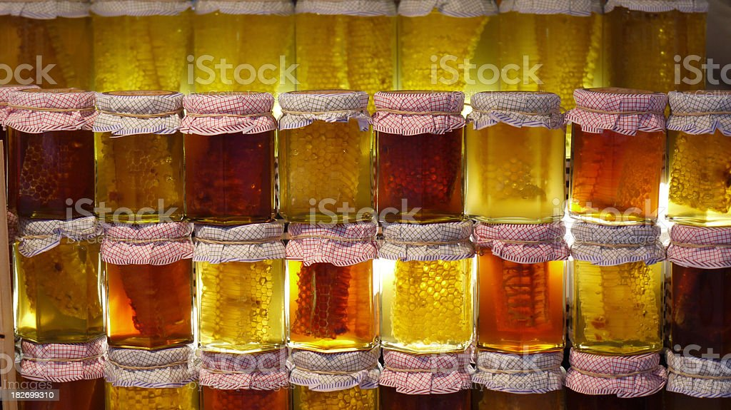 Jars of honeycomb suspended in honey royalty-free stock photo