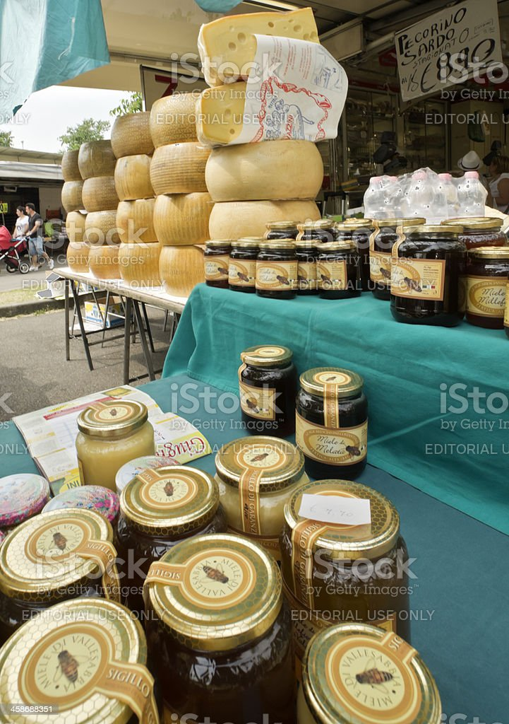 Jars of Italian honey and cheese wheels at the market stock photo