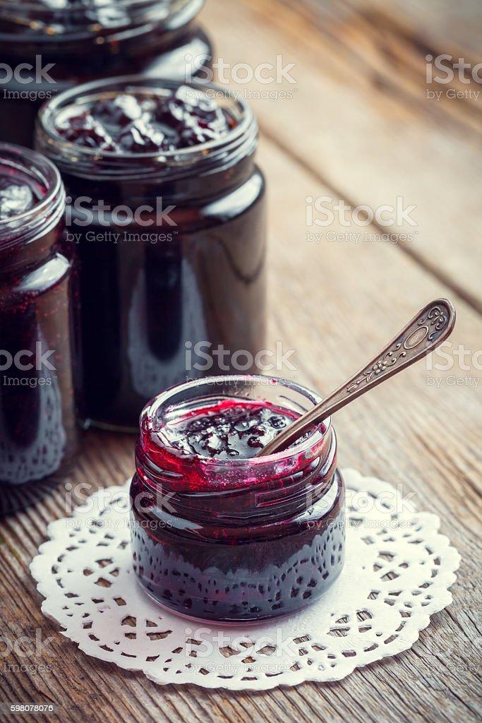 Jars of jam on wooden kitchen table. stock photo