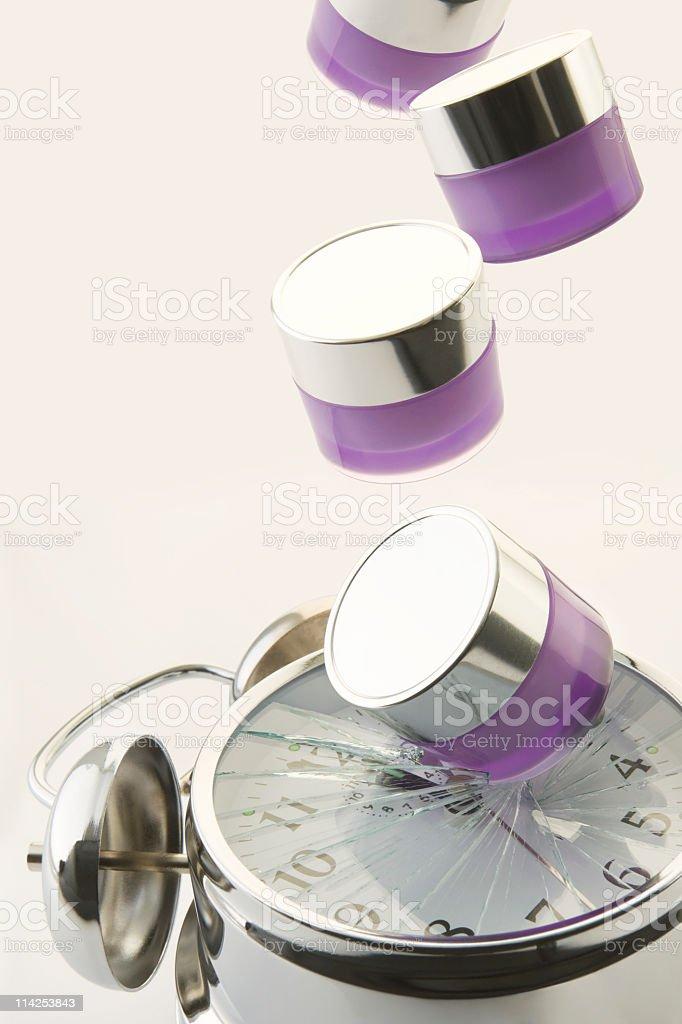 Jars of moisturiser drop and smash alarm clock face (XXL) royalty-free stock photo