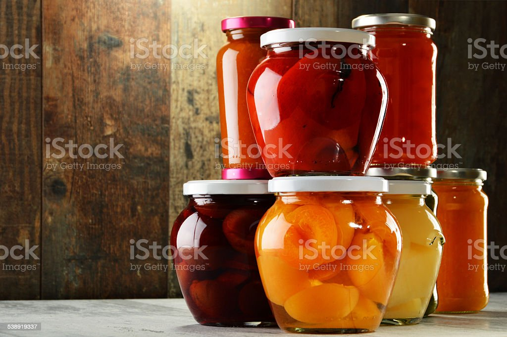 Jars with pickled vegetables, fruity compotes and jams isolated stock photo