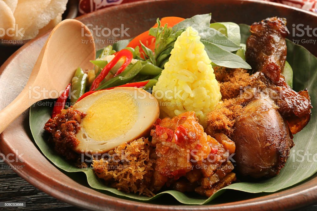 Javanese Turmeric Rice with Variety of Side Dishes stock photo