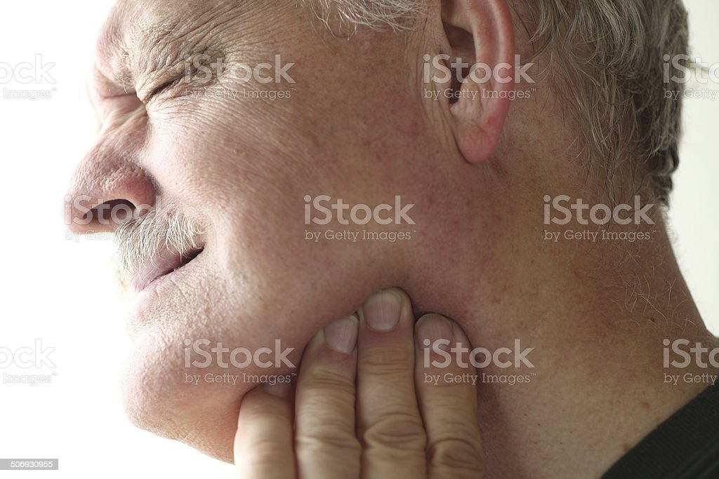 Jaw pain in older man stock photo
