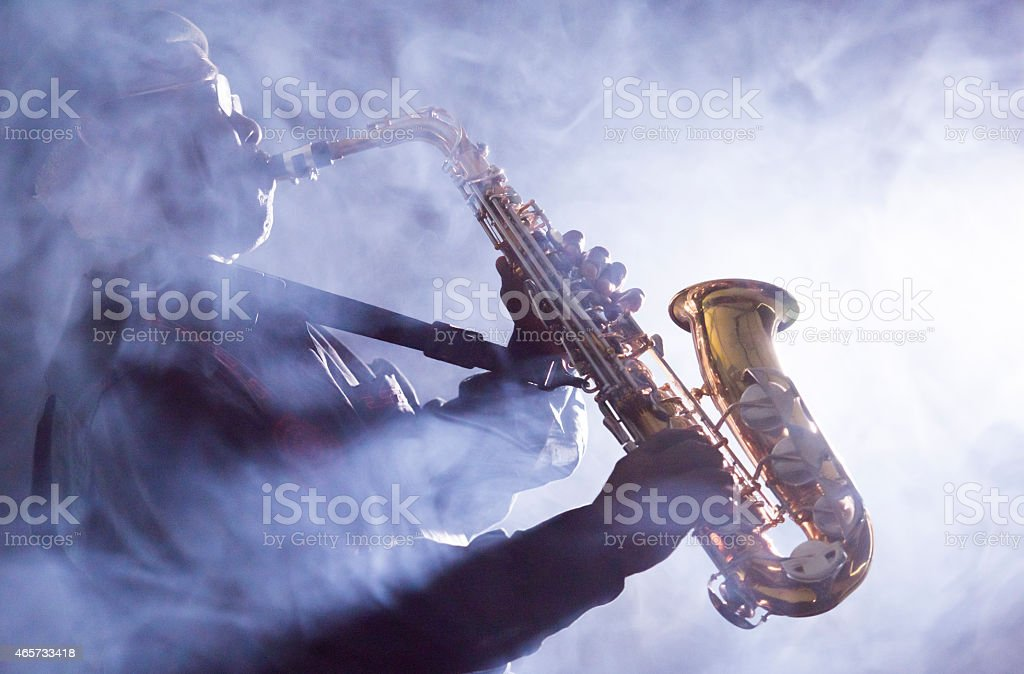 Jazz musician playing the saxophone in a smoky venue stock photo