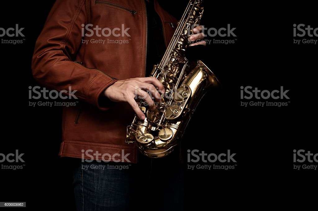 Jazz saxophone musician in the leather jacket, closeup. stock photo
