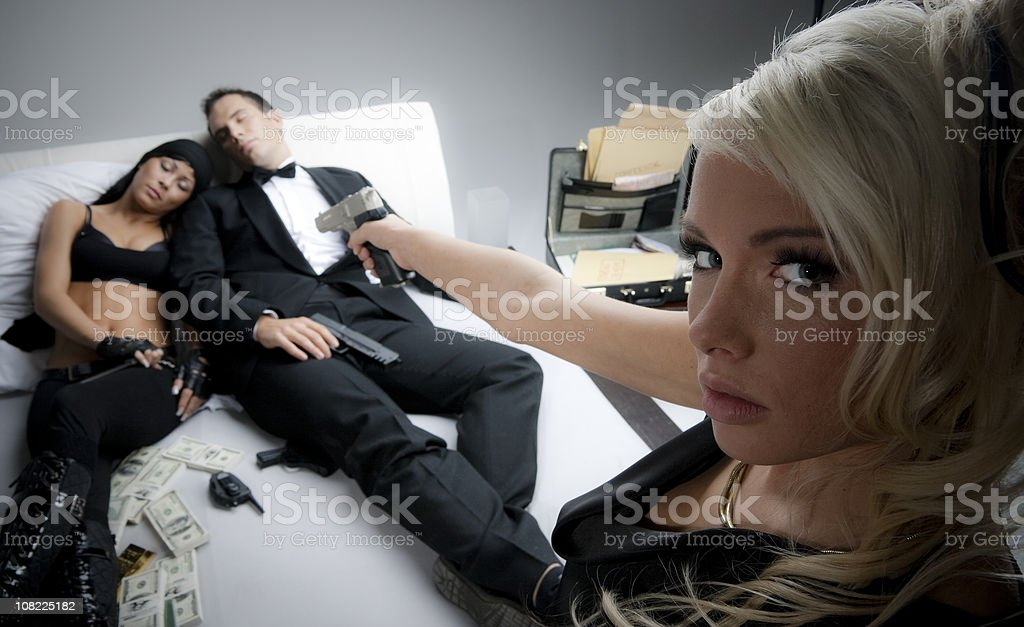 Jealous Woman Holding Gun To Couple Sleeping in Bed stock photo