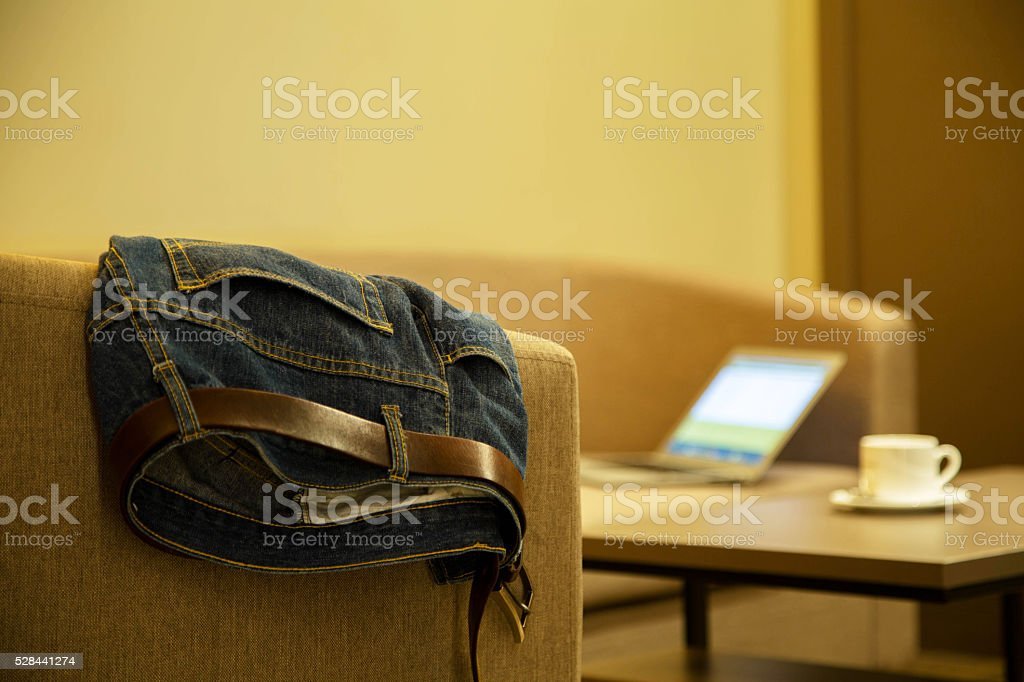 jean trousers on sofa, coffee on table stock photo