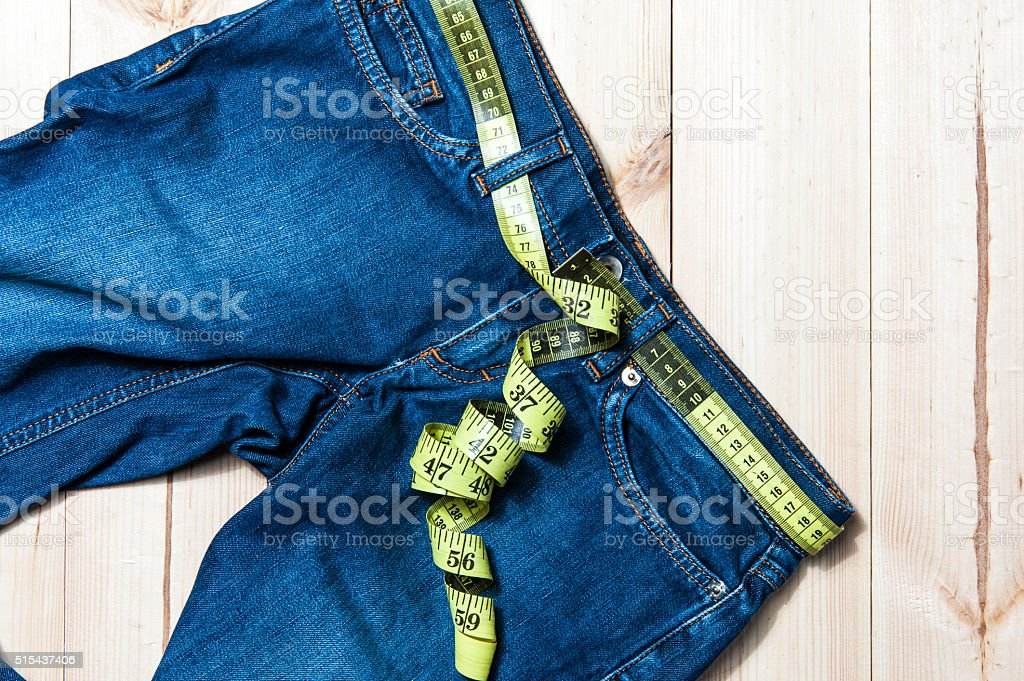 jeans and centimeter on a wooden background stock photo