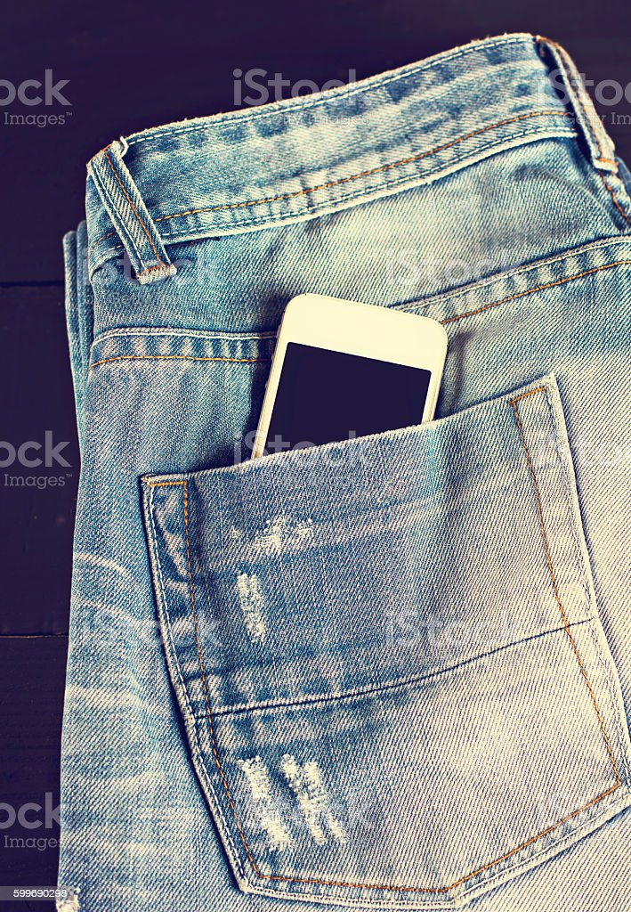 jeans and mobile phone on wooden boards. stock photo