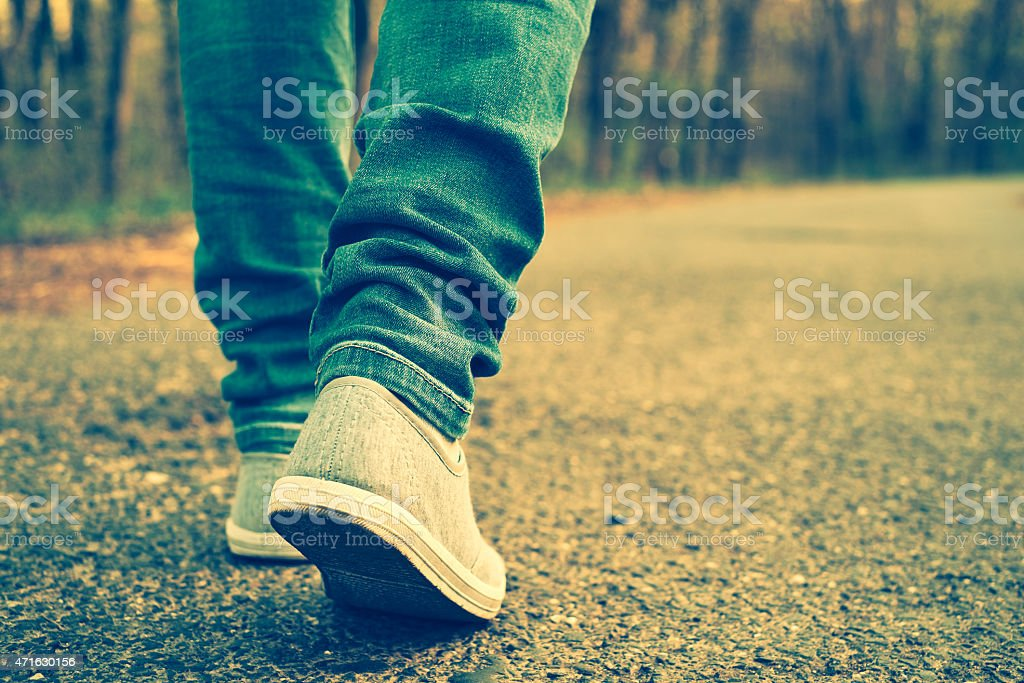 Jeans and sneakers of someone walking alone in a road stock photo