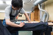 Jeans designer making custom jeans in his studio