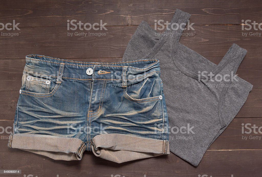 Jeans short and gray vest are on the wooden background stock photo