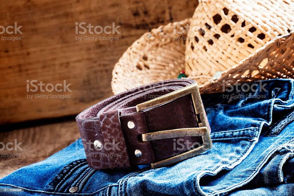Jeans, straw hat, leather belt, women's clothes in cowboy style stock photo