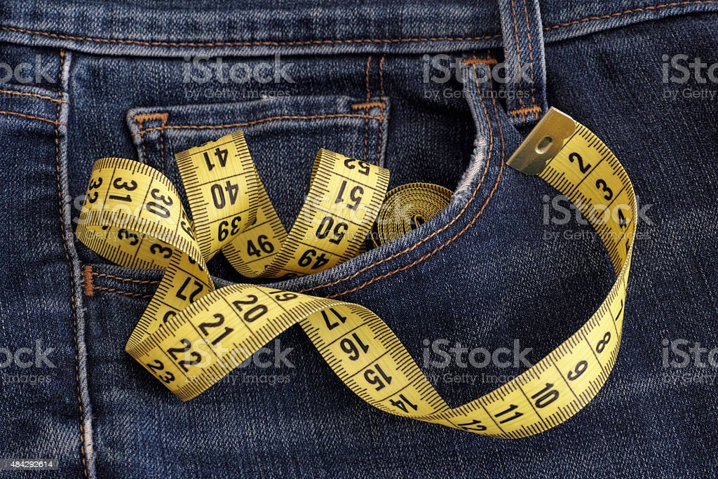 Jeans with tape measure in pocket stock photo