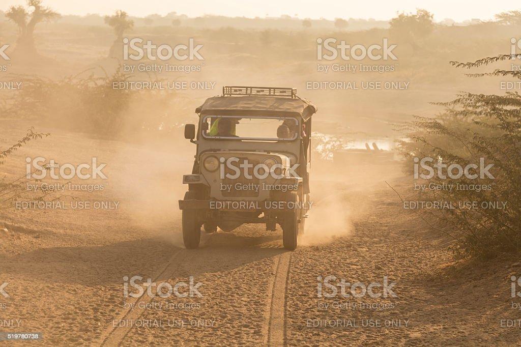 Jeep driving desert road on safari in India stock photo