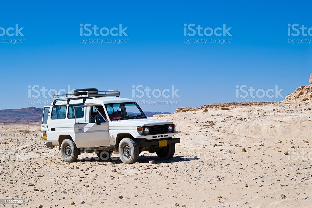 Jeep in the middle of lifeless desert royalty-free stock photo