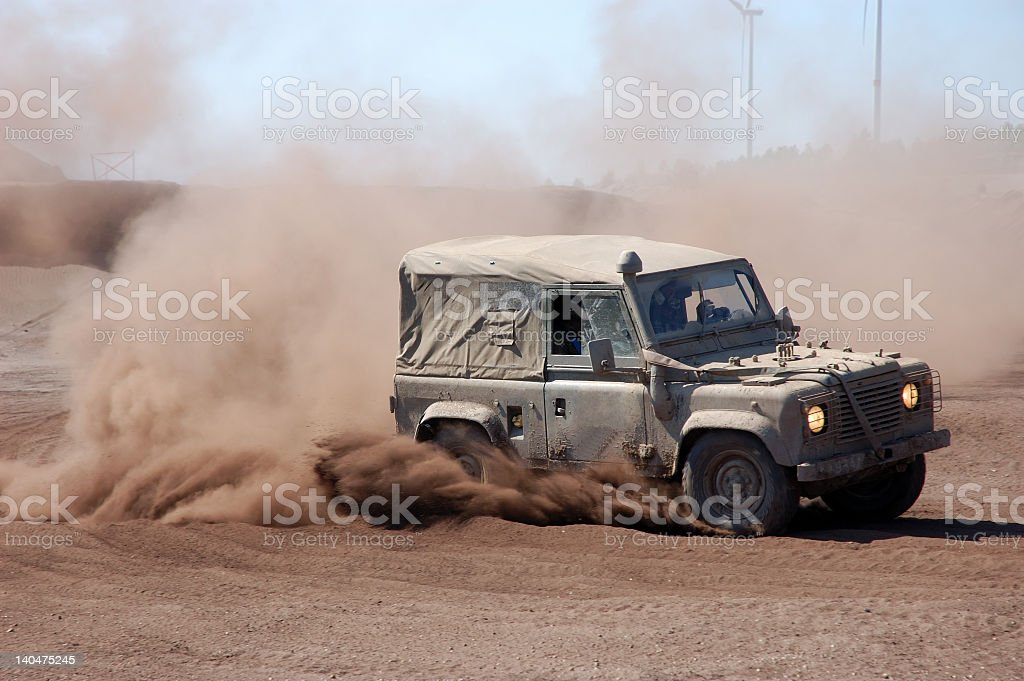 Jeep with a trail of sand in an off-road race stock photo