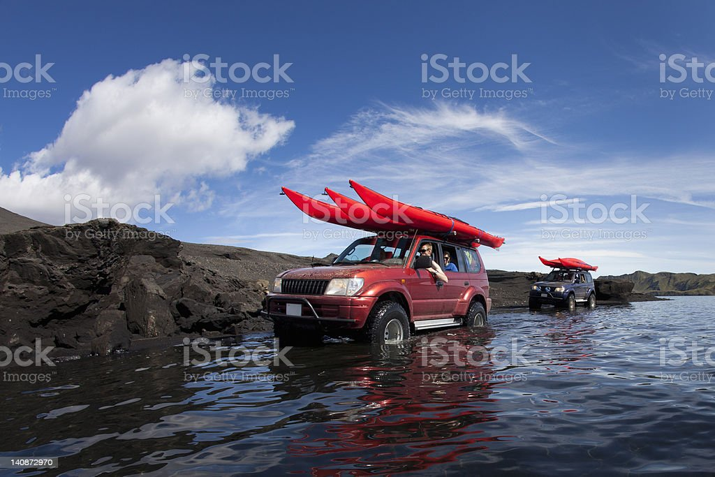Jeeps driving through shallow lake stock photo