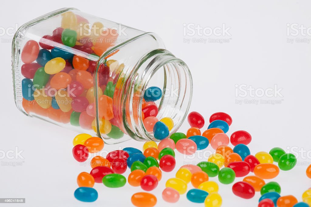 Jelly Beans spilled from glass jar isolated on white background stock photo