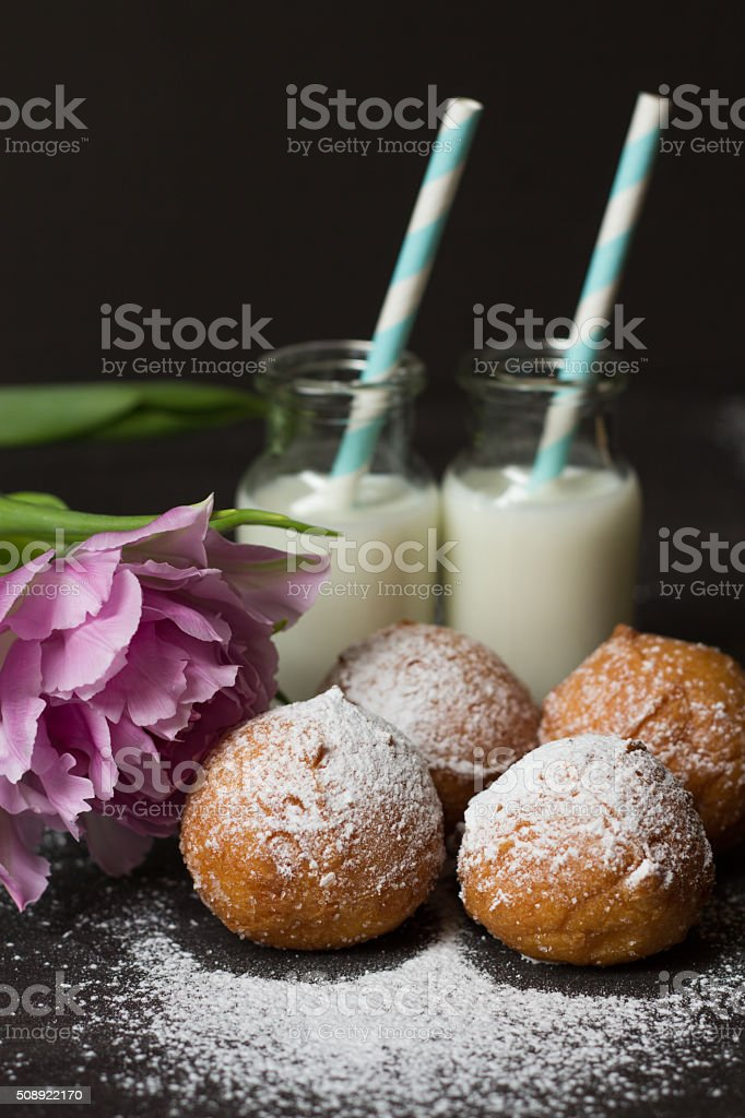 Jelly doughnuts, pink flower and two bottles of milk stock photo