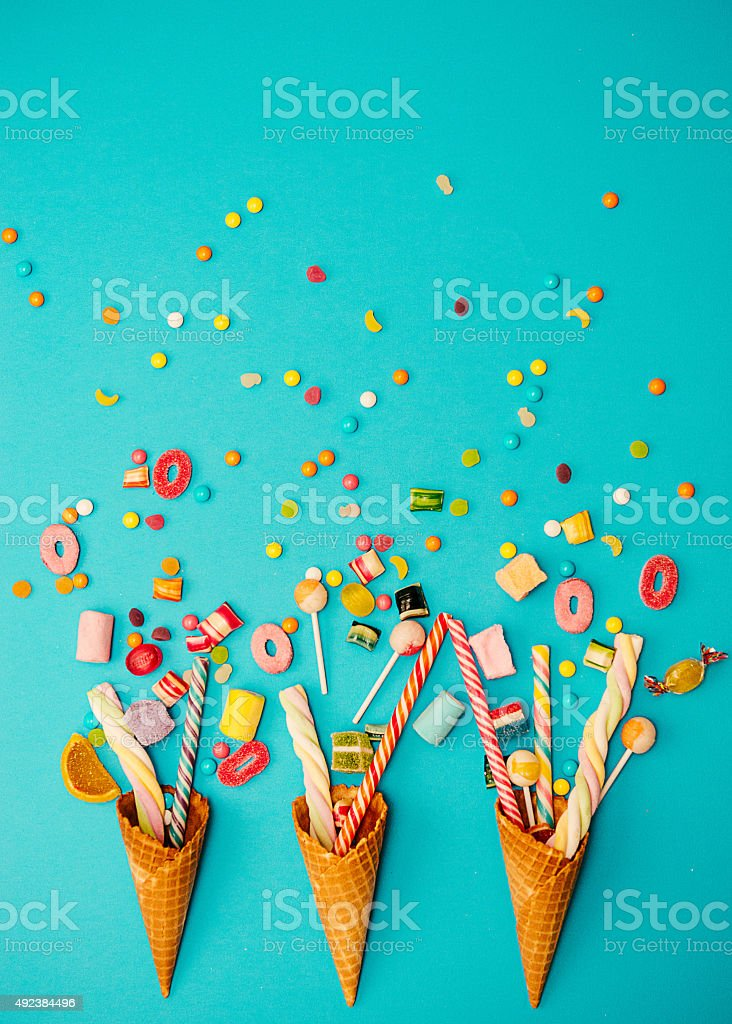 Jellybeans and gummy candy, vintage sweet food concept on blue stock photo