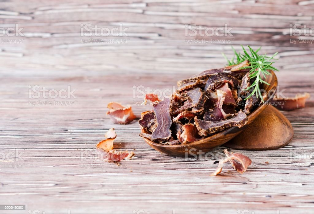 jerked meat, cow, deer, wild beast or biltong in wooden bowls on a rustic table stock photo