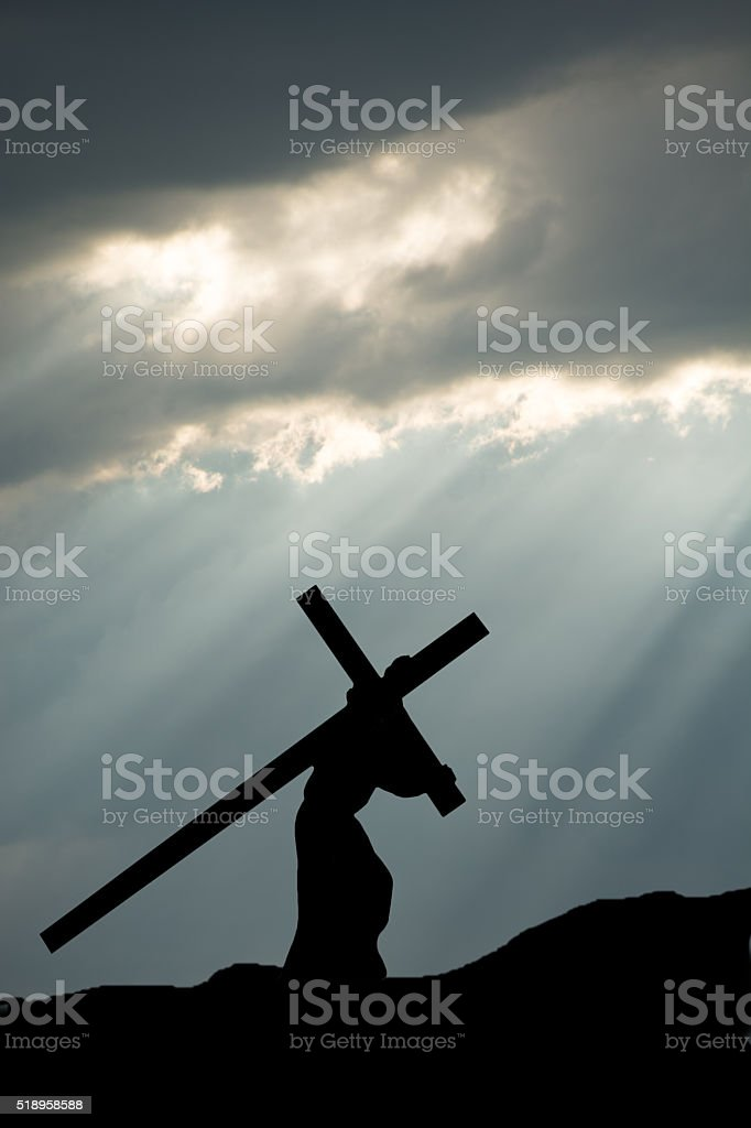 Jesus carrying the Cross with dark and moody sky stock photo