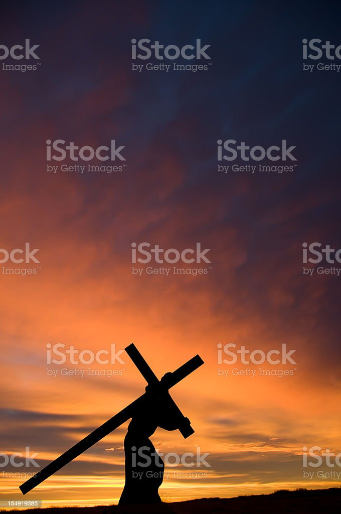 Jesus Carrying the Cross with Orange Sunset ... Vertical stock photo
