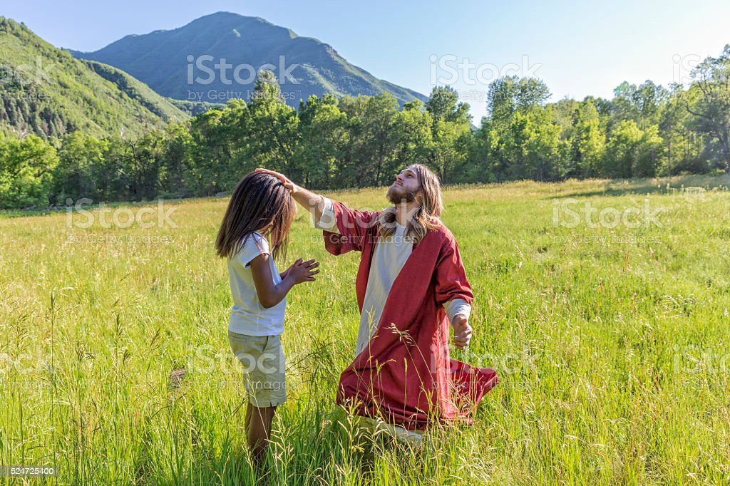 Jesus Christ Prays with a Child in a Field stock photo