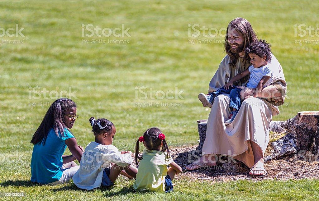 Jesus Christ Sitting Teaching Four Children Siblings stock photo