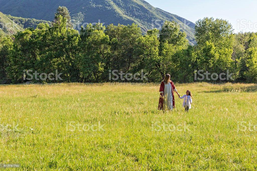 Jesus Christ Walks with a Child ina Field stock photo