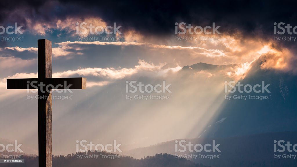 Jesus Christ wooden cross on a dramatic, colorful sunset stock photo
