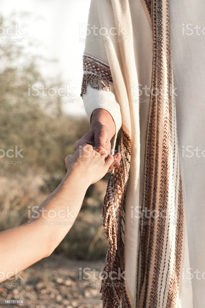 Jesus holding a persons hand outdoors stock photo