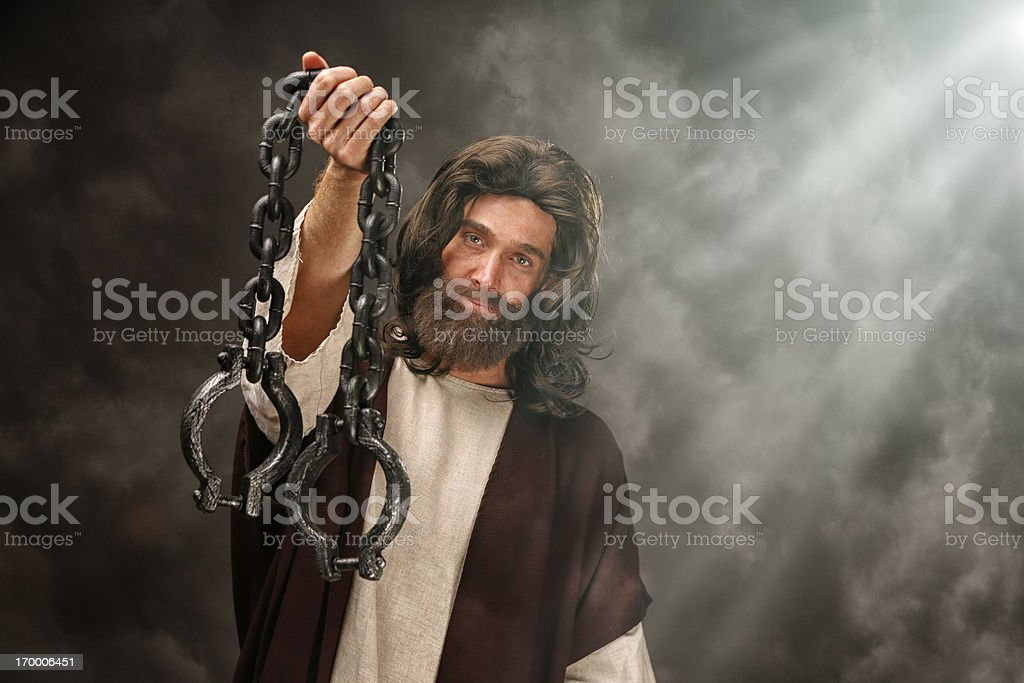 Jesus holding loose chains stock photo